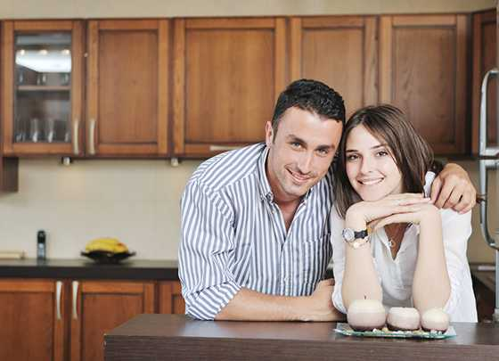 happy young couple have fun in modern wooden kitchen